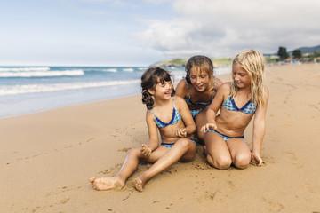 Spain, Colunga, three girls sitting on the beach having fun