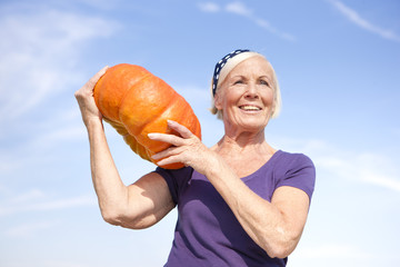 Germany, Saxony, Senior woman carrying pumpkin on shoulder