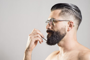 Dark haired man combing beard