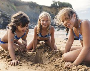 Spain, Colunga, three girls playing on the beach