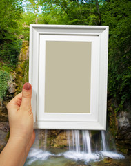 Wooden frame in woman hands on the background waterfall in forest