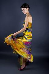 Female waving her colorful yellow tie dye dress skirt around