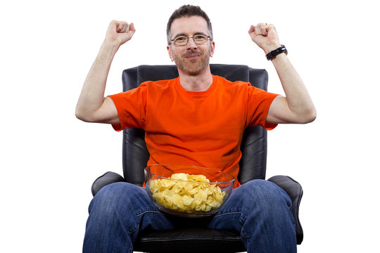 Front view of man watching TV while eating potato chips