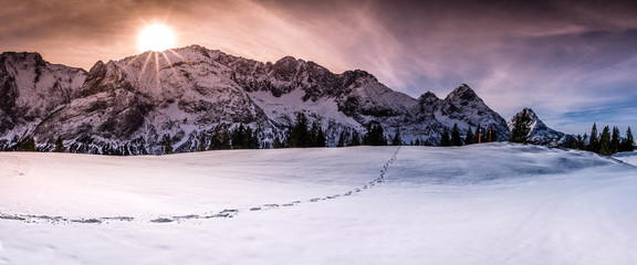 Winter landscape with Austrian alps peaks, a single trail of footsteps on snow, under a dramatic and colorful sky.