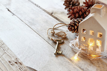 image of small miniature house and old key over rustic wooden table