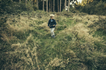 Little boy exploring forest, walking in grass with his stick