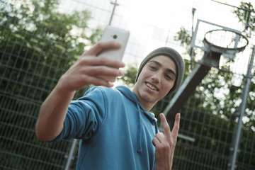 Cool boy taking selfie outdoors