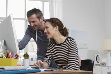 Man and woman at home sitting at desk with computer