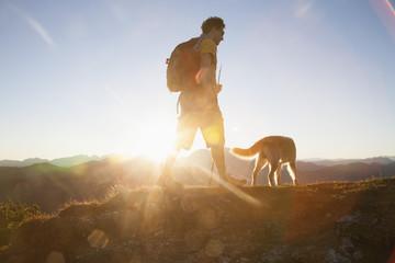 Austria, Tyrol, Unterberghorn, hiker with dog at sunrise