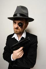 crazy beard detective whit gun in hat