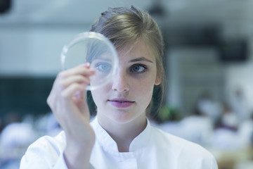 Young female natural scientist watching bacteria culture in petri dish at microbiology laboratory