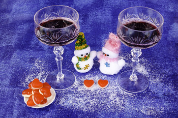 Two snowmen, glasses of wine and a saucer with red hearts.