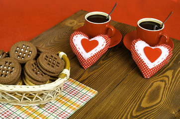 Two cups of coffee, a basket of biscuits and two hearts.