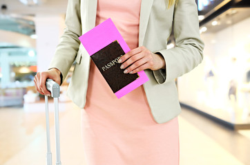 Woman with passport and suitcase in airport