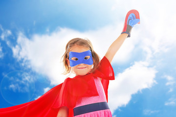 Superhero little girl on sky background