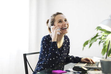 Young woman telephoning with smartphone at home