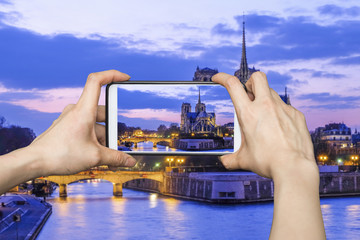Girl taking pictures on mobile smart phone in Notre Dame at the