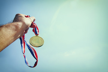 man hand raised, holding gold medal against skyl. award and victory concept. selective focus. retro style image.