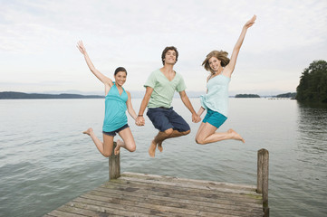 Germany, Bavaria, Starnberger See, Young people jumping on jetty, laughing, portrait