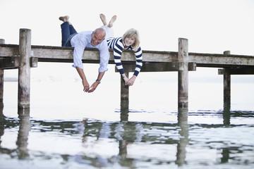 Germany, Bavaria, Starnberger See, Senior couple lying on jetty, smiling, portrait