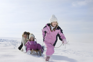 Germany, Bavaria, Munich, Girl (8 9) pulling sister (4 5) on sledge, mother in background