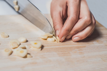 Hand cutting garlic on wooden desk