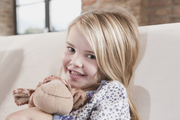 Germany, Cologne, Girl (4 5) with a stuffed toy, sitting on sofa