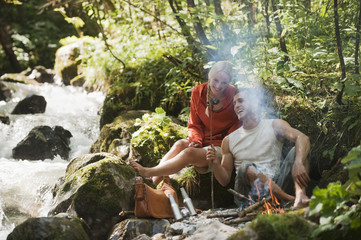 Austria, Steiermark, Young couple sitting at camp fire by stream in forest