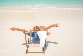 Woman suntanning on the beach in Thailand