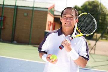 filipino man holding a tennis racket and ball