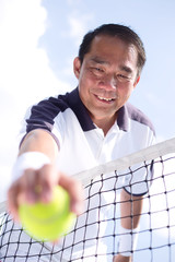 filipino tennis player picking up a ball from behind the net