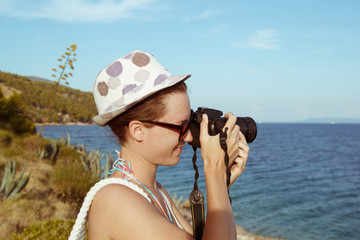 Young woman photographer, tourist using digital camera taking photo by the sea