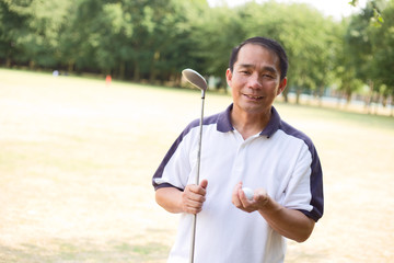 golfer holding a club and golf ball
