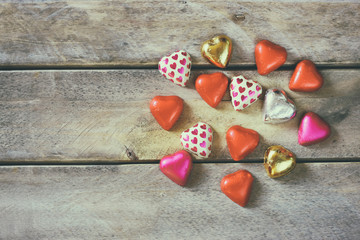top view image of colorful heart shape chocolates on wooden table. valentine's day celebration concept