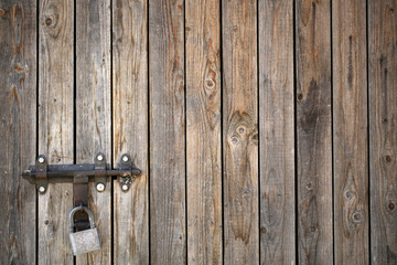 Old wooden gate with padlock