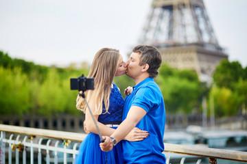 Beautiful young dating couple in Paris making selfie