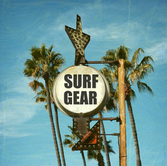aged and worn vintage photo of surf gear sign