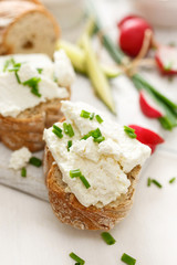 Canapes with curd cheese and fresh chive on a white table. Delicious and healthy breakfast
