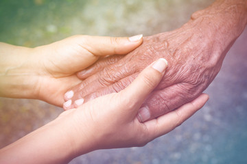 Senior and young holding hands with vintage color tone