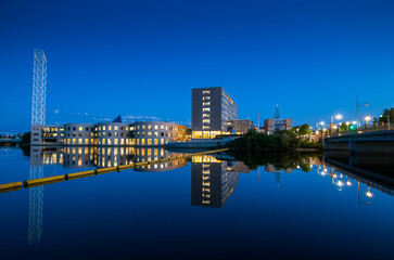 Rideau river and old city hall. Calm, glass-like water reflects former Ottawa city hall buildings.  Clear spring and summer evenings in the park, city of Ottawa, Ontario.