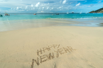 Happy new year written in the beach