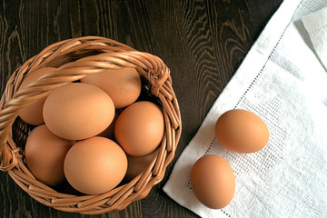 Eggs.  Chicken eggs in a wicker basket and two eggs on a napkin on a dark wooden background.