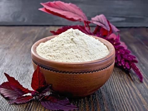 Flour amaranth in clay bowl on dark board