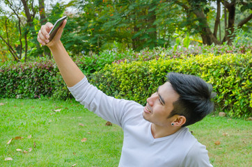 Man taking a selfie with his smart phone outdoor