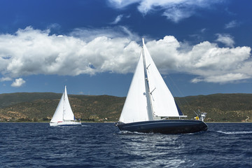 Sailing ship yachts with white sails in a row on the sea.