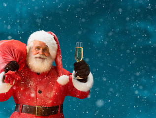 Santa Claus carrying big bag full of gifts with a glass of champagne and looking at camera / Merry Christmas & New Year's Eve concept / Closeup on blurred blue background.