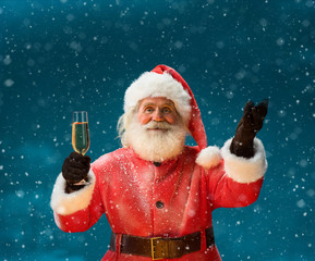 Santa Claus with a glass of champagne and looking at camera / Merry Christmas & New Year's Eve concept / Closeup on blurred blue background.