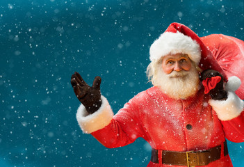 Smiling Santa Claus, carrying big bag full of gifts to children / Merry Christmas & New Year's Eve concept / Closeup on blurred blue background.