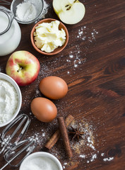 Ingredients and tools for baking - flour, eggs, butter, apples, cinnamon on a brown rustic wooden surface.