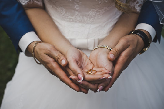 The groom hugging the palm of the bride with rings 4815.